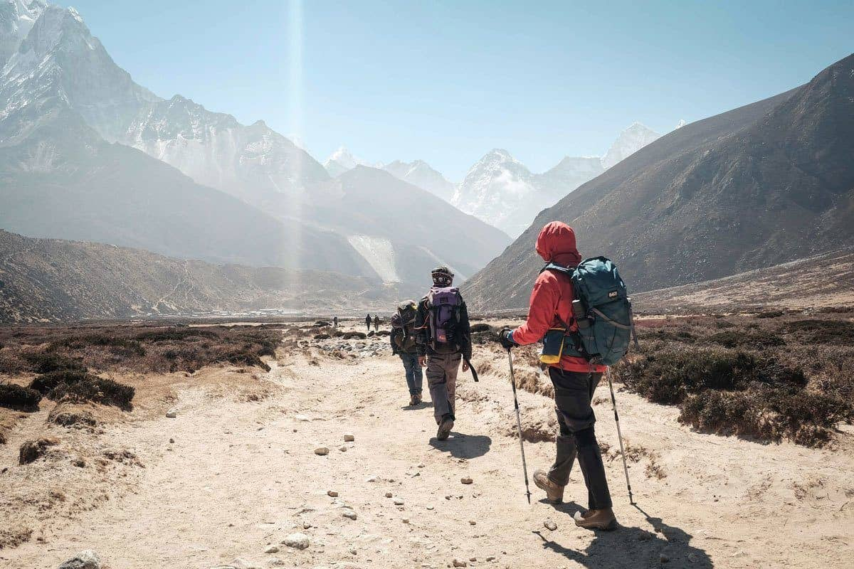 String of walkers with snow capped mountains in the background.