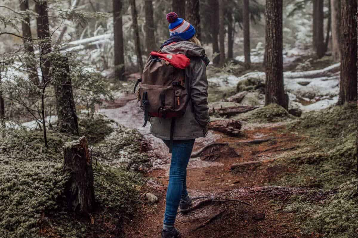 Hiker in beanie and backpack walking through frosty forest.
