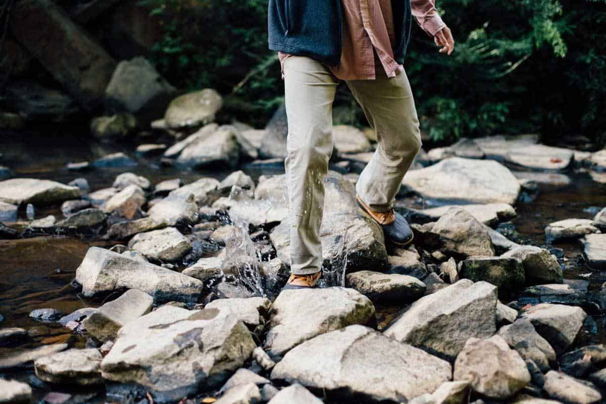 Man in hiking boots and quick dry pants walking on rocks to cross a stream.
