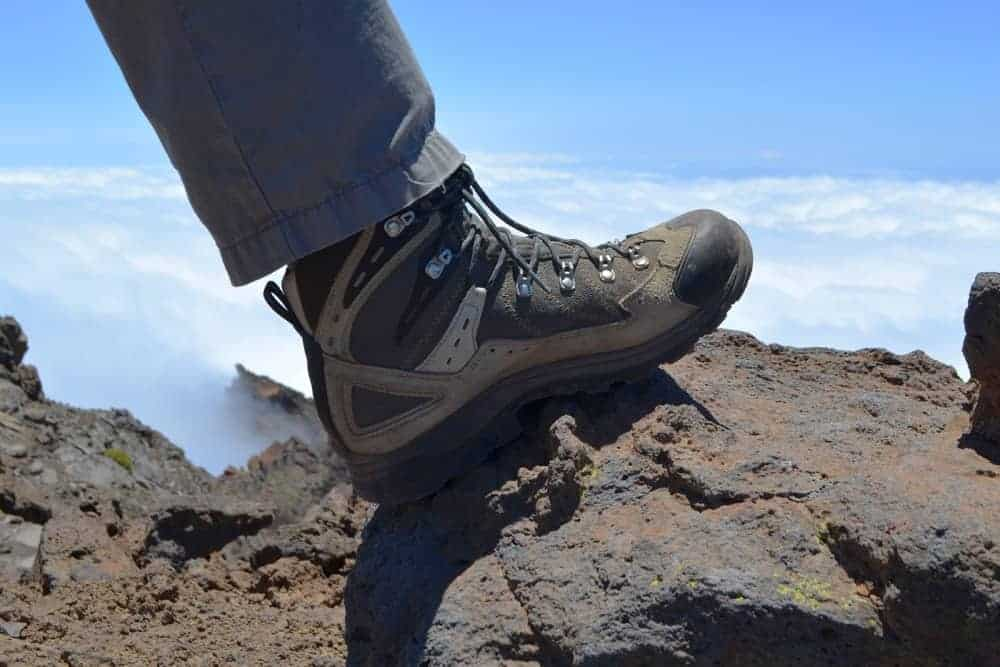 Mans hiking boot on a rock on a mountain.
