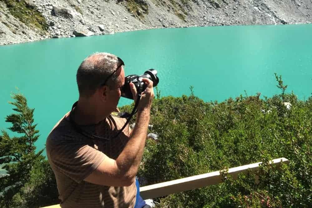 Man holding camera taking a shot across a lake.