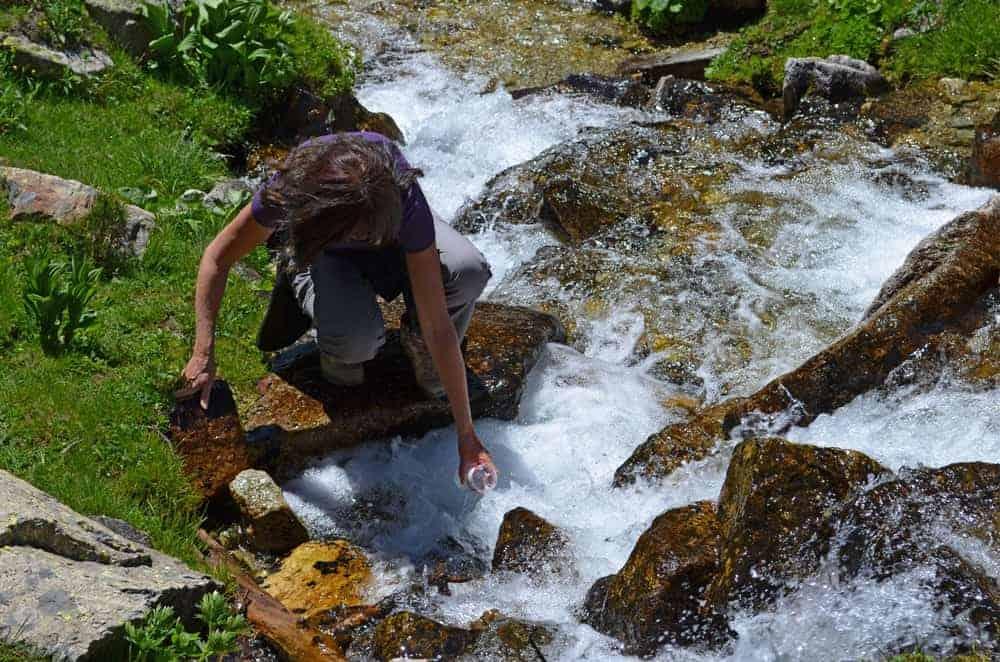 Walker filling water bottle from a flowing stream.