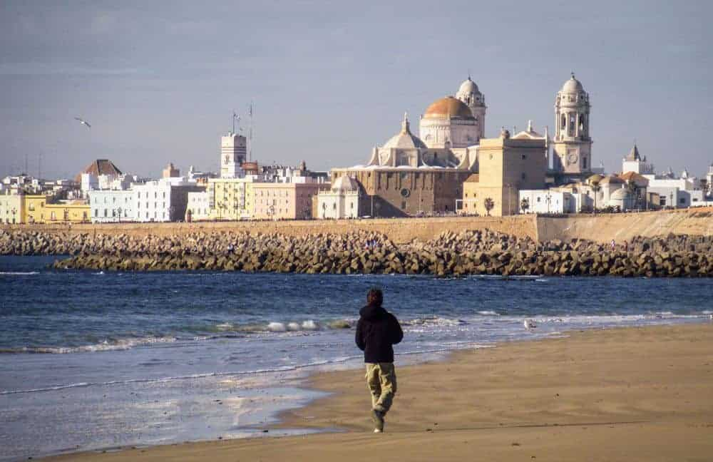 man walking on the beach in Cadiz. Looking for free things to do in Cadiz, the beach is a great choice. Add this to your Seville itinerary and do a Day trip from Seville to Cadiz