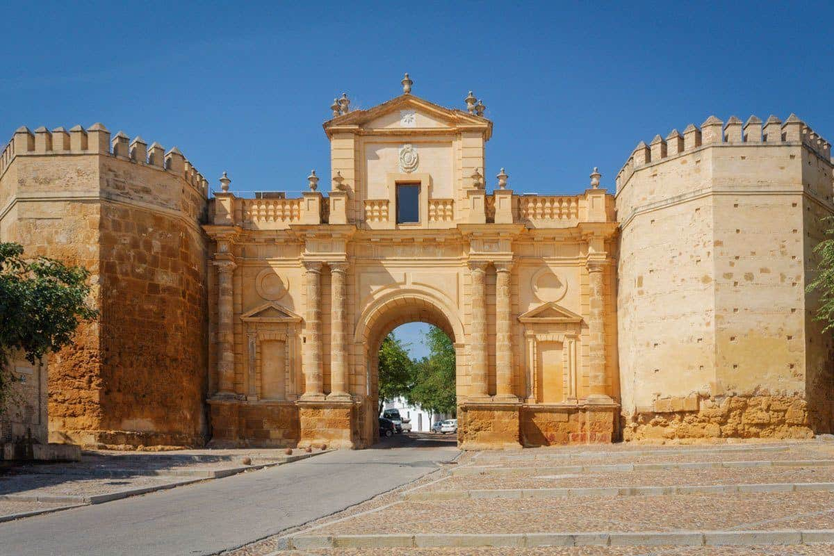 Sandstone pillars and ornate stone entrance to Carmona. Best thing to do in Carmona is to visit this gate. this is one of the best Day trips from Seville to Carmona