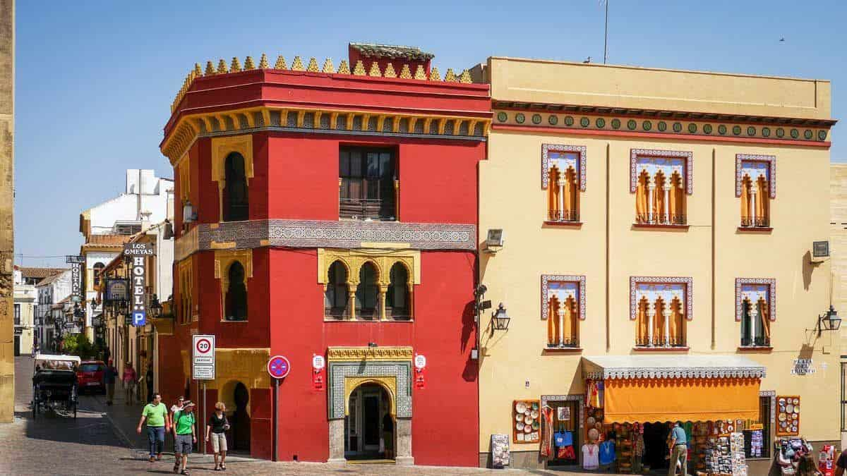 Colourful red and yellow street corner with tourists wandering past. Add Cordoba to your best Day trips from Seville itinerary