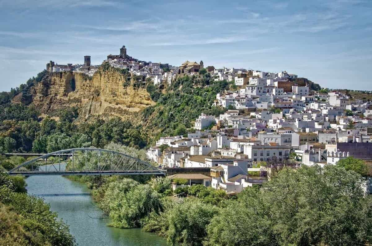 Sprawling white village of Ronda next to the river with steep cliffs. Want a great free thing to do in Spain, just go to Ronda and walk around. This is why we say to do a Day trip from Seville to Ronda