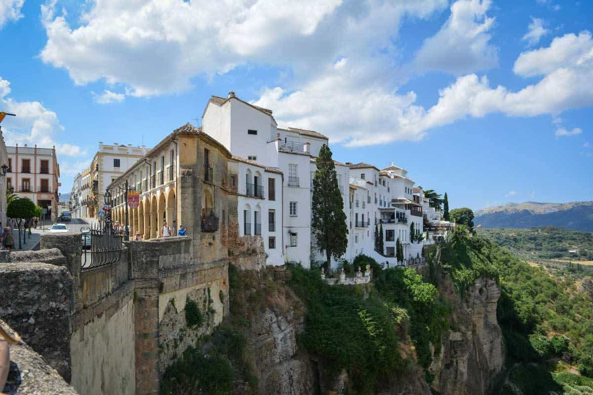 Tourist taking photos from stone bridge in Ronda. Looking for the best things to do in Ronda, it is a photographers dream and that is why you should do Day trips from Seville to Ronda