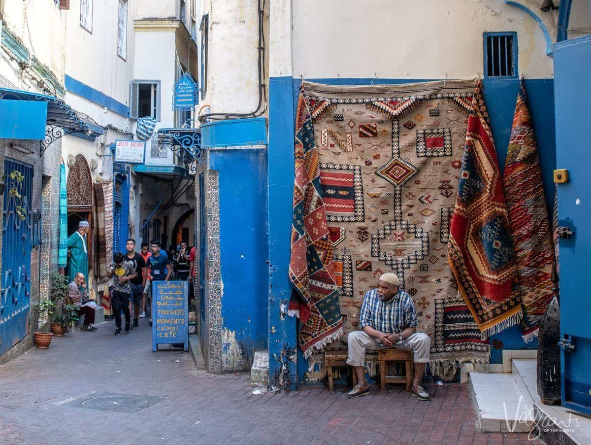 Stall owner sitting in front of rugs in the streets of Tangier. You probably never thought of adding a Day trip from Seville to Tangier in your Seville itinerary.