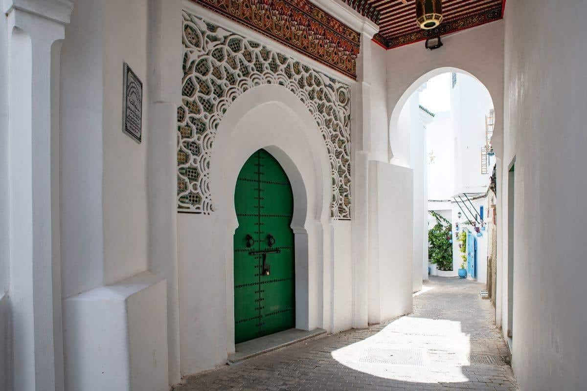 Green door set in white ornate wall in Tafira. Seeing Tafira by foot is the best free thing to do in Tangier on your Day trips from Seville to Tangier, Morocco
