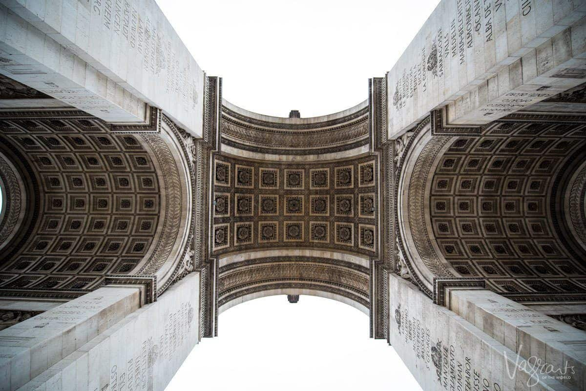 looking up at the arch of the arc de triomphe. angles are one of the best Travel Photography Tips for Getting the Best Landmark Shots