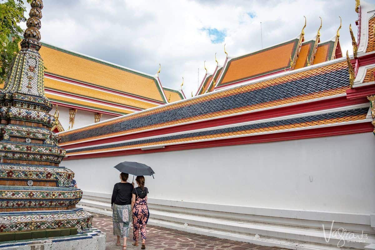 two women walking around a multicoloured shrine in bangkok. having people in your shot will help with getting the best travel photographs