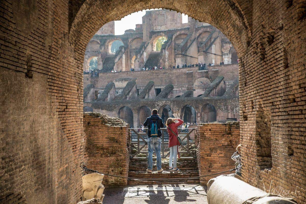 two people in an archway overlooking the colosseum in rome taking photographs. getting the right composition is very important when you want to get the best travel photos.
