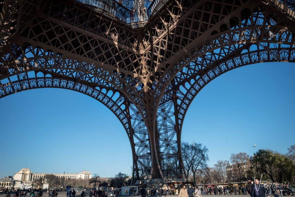 under an arched leg of the eiffel tower. giving thought to composition is one of the best Travel Photography Tips for Getting the Best Landmark Shots