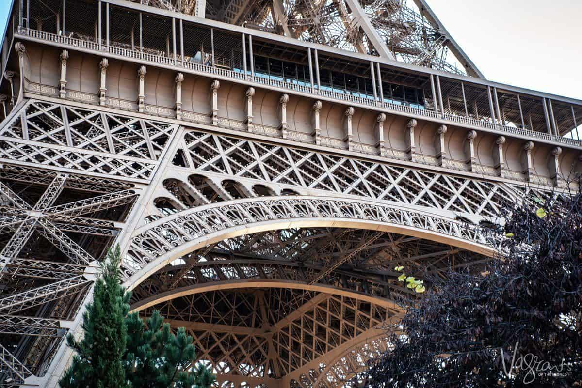 looking up from the outside at an arched leg of the eiffel tower. giving thought to composition is one of the best Travel Photography Tips for Getting the Best Landmark Shots