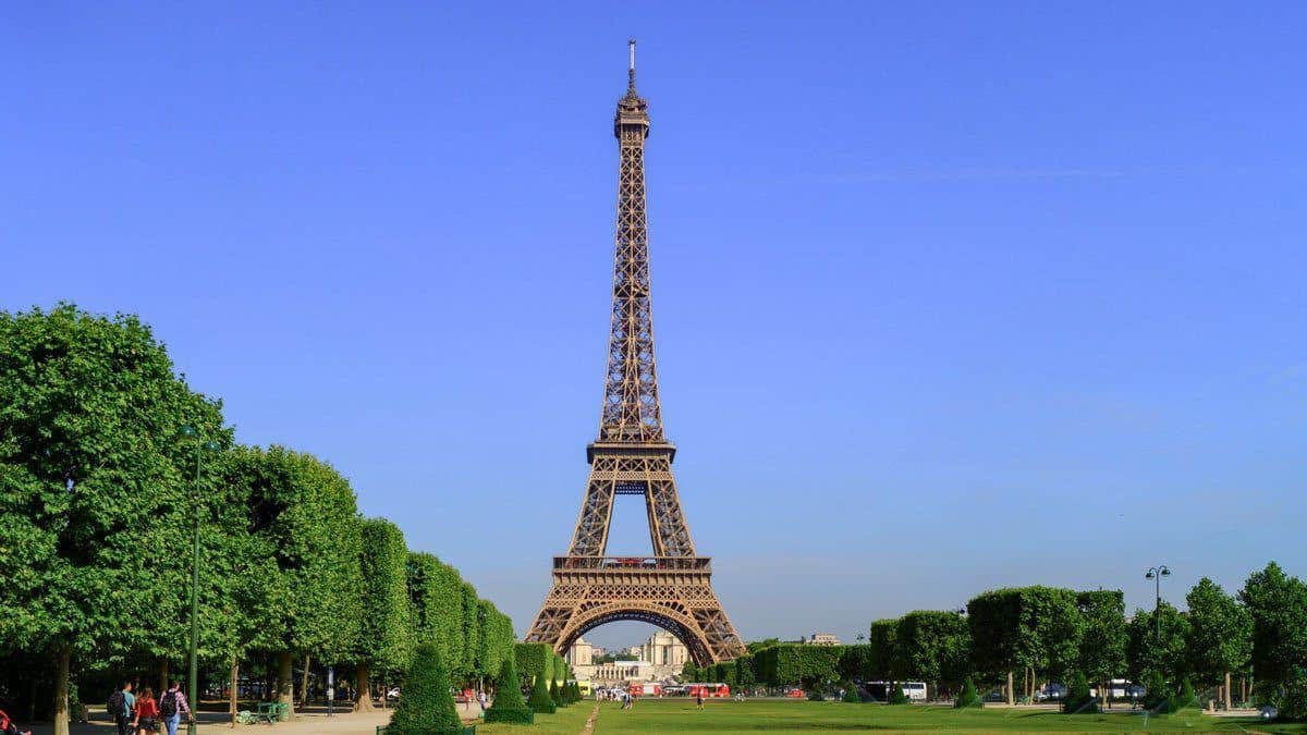 the Eiffel tower with blue skies and green trees to the side. giving thought to composition is one of the best Travel Photography Tips for Getting the Best Landmark Shots