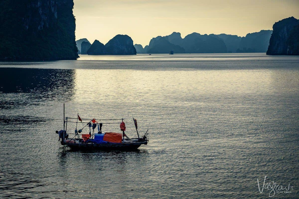 a junk floating across halong bay with large rock formations erupting from the water in the background. Sometimes just being in the right place and knowing it is a landmark and travel photography tip