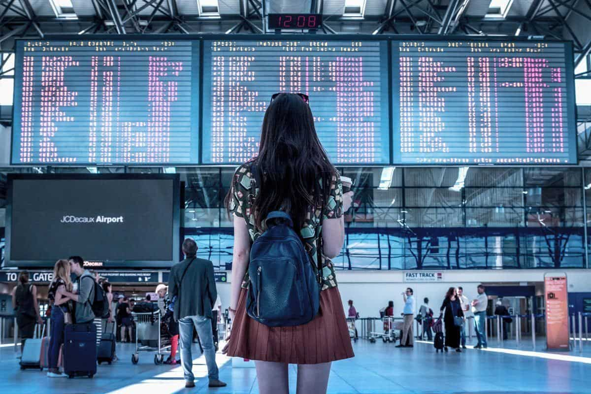 girl holding coffee looking at airport departures board. travellers often ask how to how to Reduce Homesickness Abroad. we have some of the Best Home Comforts for Travel