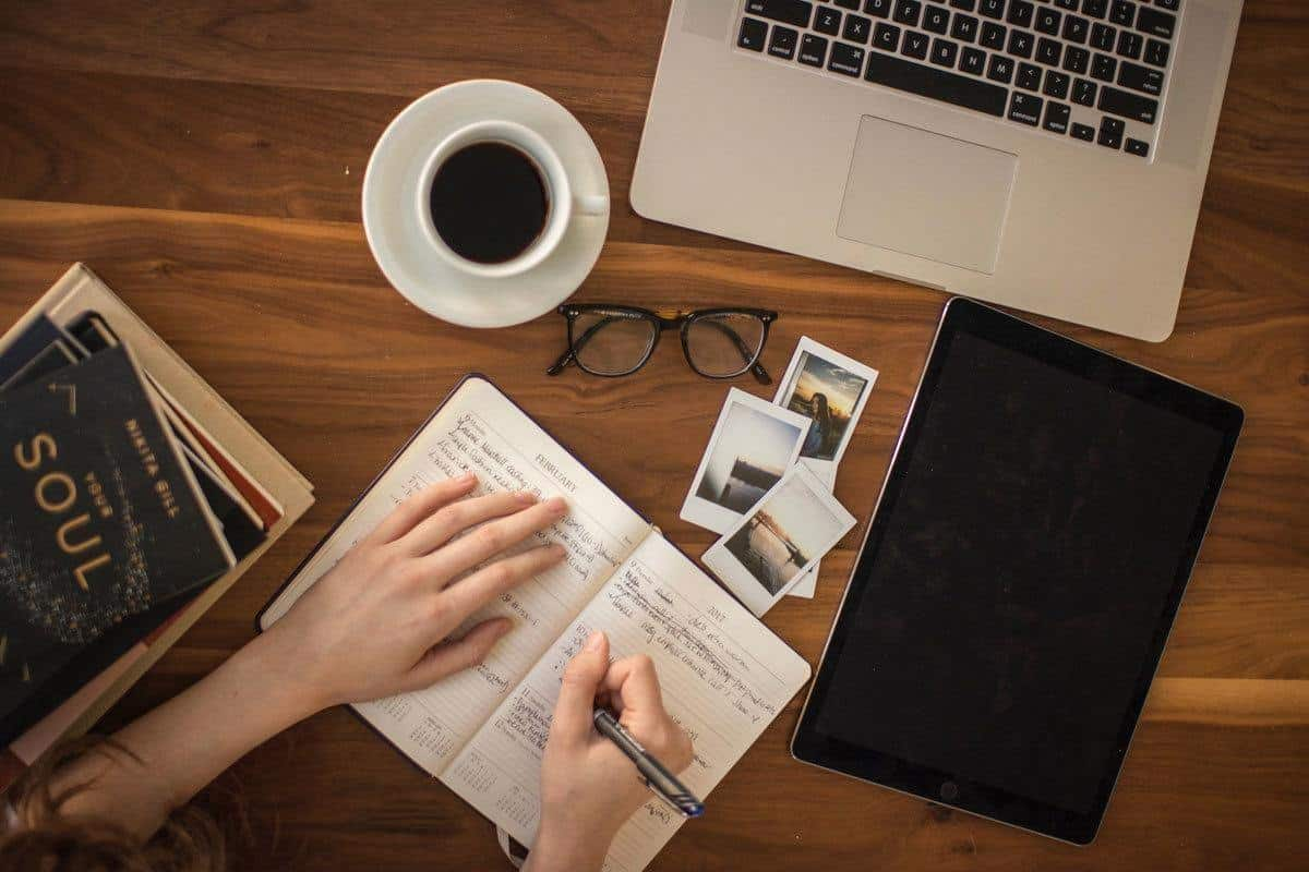 person writing in diary on a table with photos, coffee and a laptop. travellers often ask how to Reduce Homesickness Abroad. we have some of the Best Home Comforts for Travel