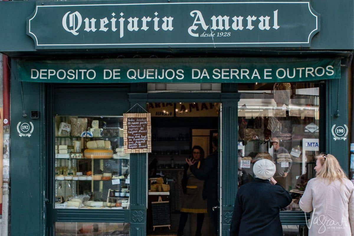 Two people admiring the cheese in the window of Queijaria Amaral Porto's oldest cheese shop.