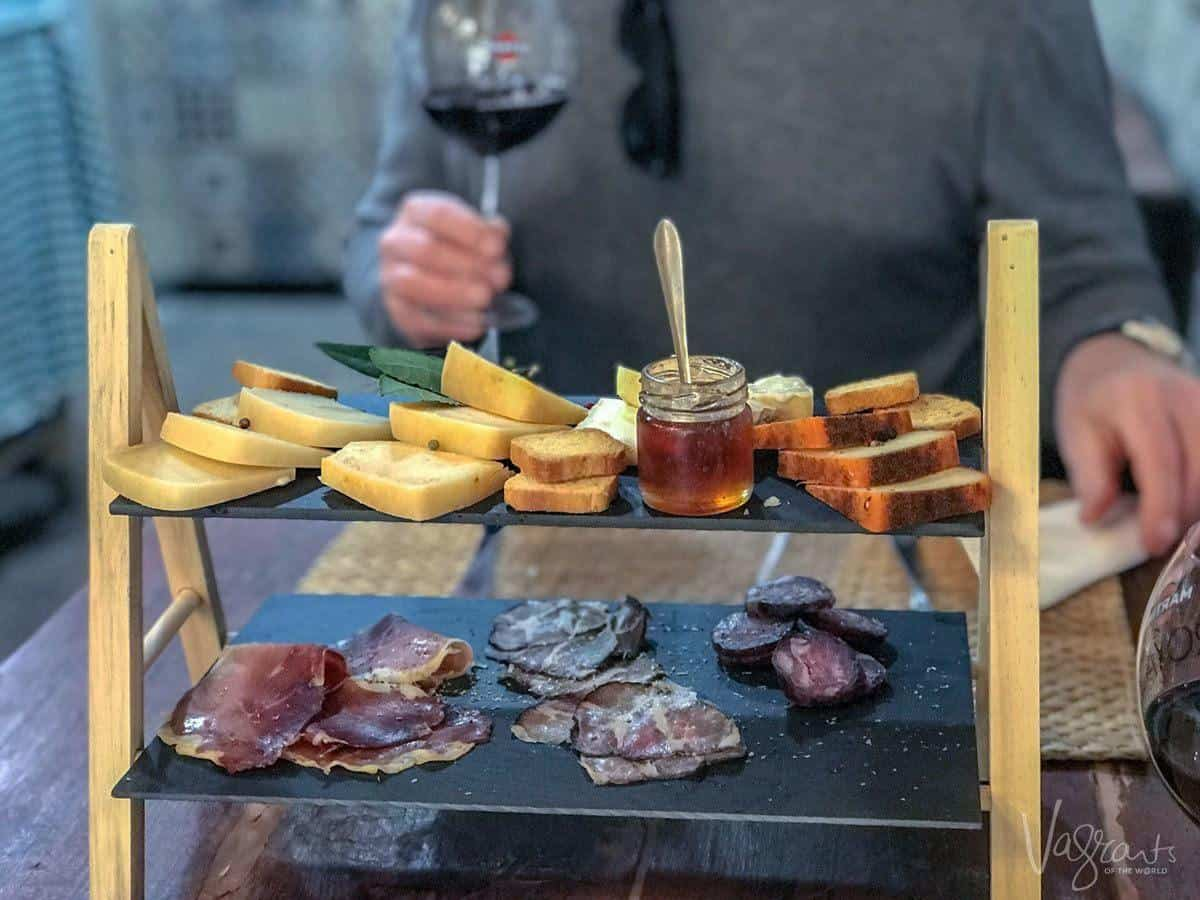 A two level cheese and meat platter at Queijaria Amaral Porto's oldest cheese shop. Put this as number 1 place to eat in porto on your porto itinerary