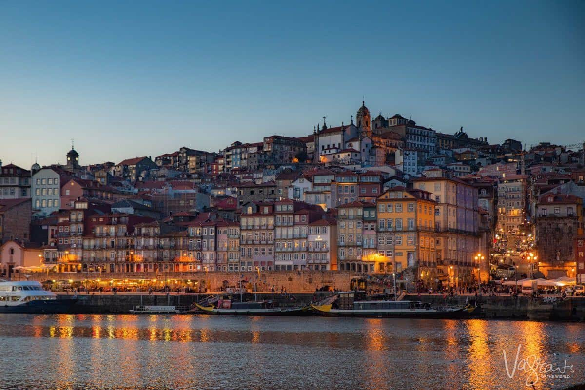 Douro river and lit buildings of the Ribeira neighborhood in the early evening, an area which is the best area to stay in Porto Portugal