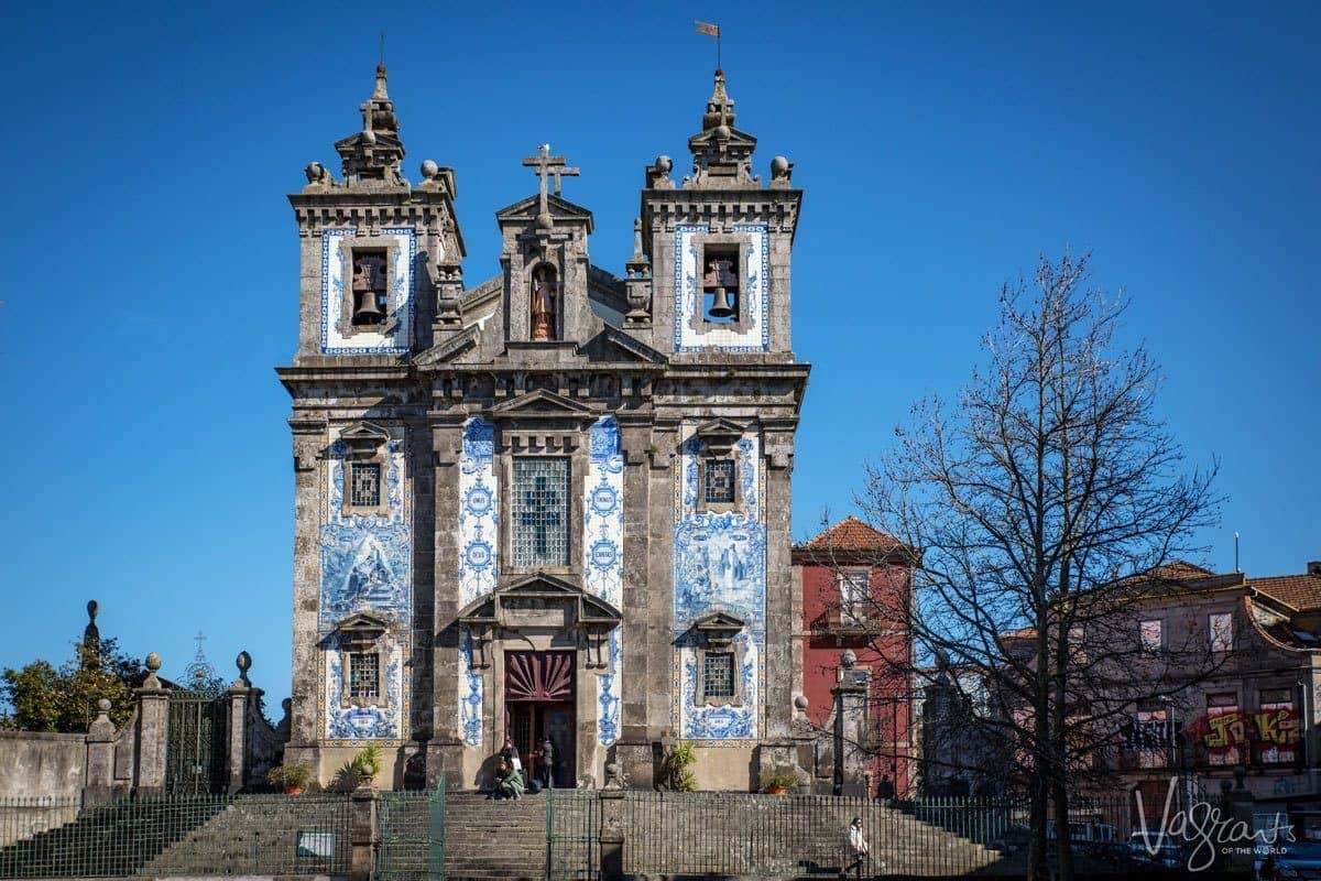 The stone towers and blue and white tiles of the ornate Church of Saint Ildefonso.
