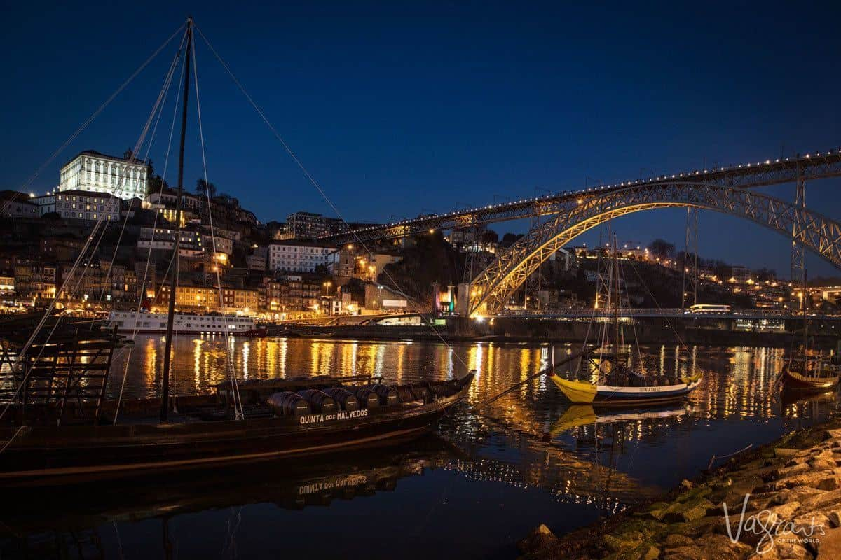 A night view of the river and the illuminated D. Luis I bridge with a port boat in the foreground.
