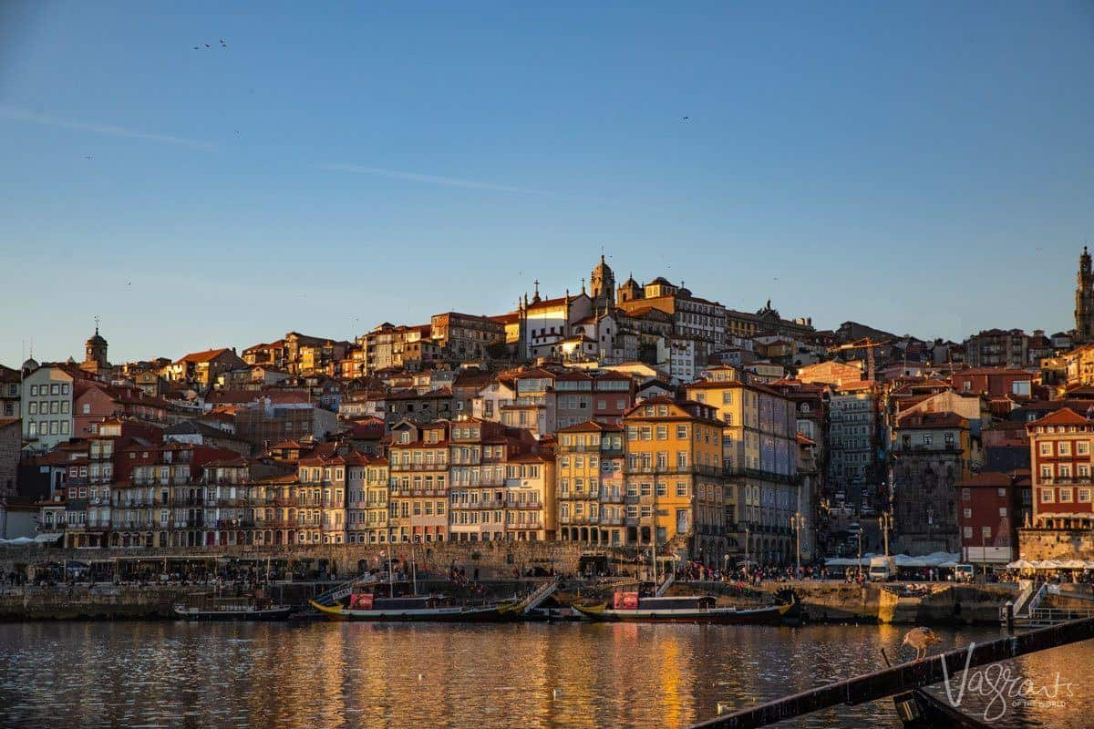 Porto city colours change across the river as the sunsets casting shadows on the multicoloured buildings rising back from the river Douro.