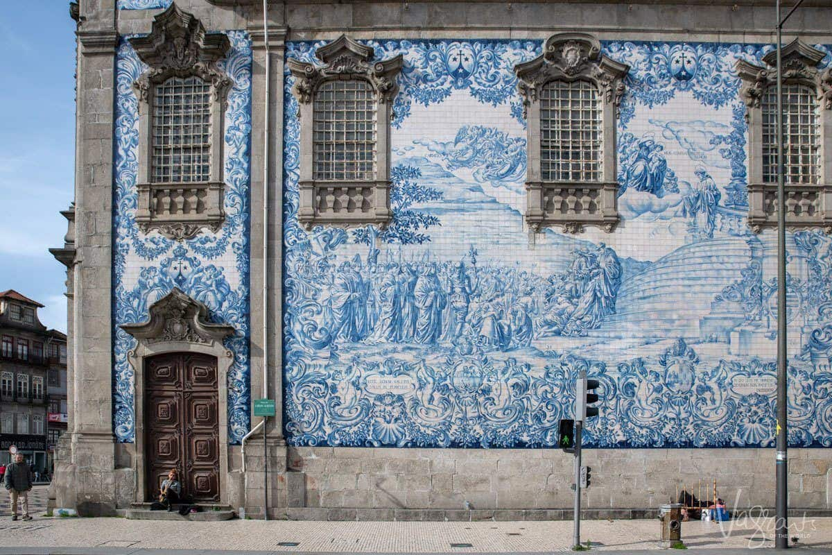 Person sitting on the steps of the blue and white tiled Igreja do Carmo.