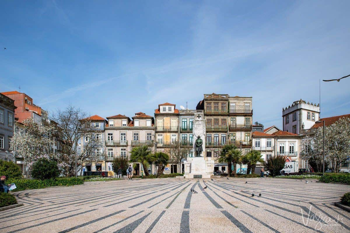 Cobblestoned park with central statue surrounded by colourful houses in the centre of Porto. Weekend markets are often held in these squares and make these areas the best area to stay in Porto Portugal.