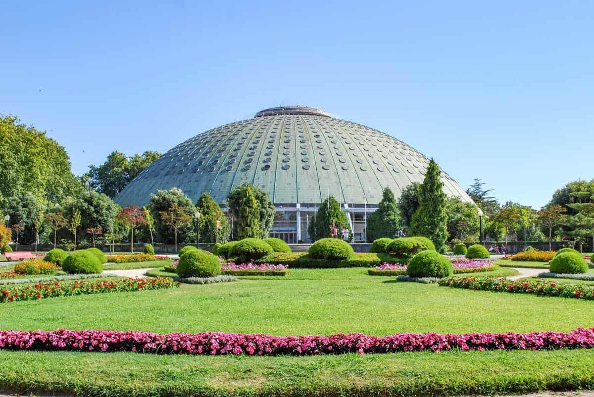 The green grass and flower beds in front of what looks like a flying saucer in the Porto Jardins do Palacio de Cristal, another fantastic porto attraction.