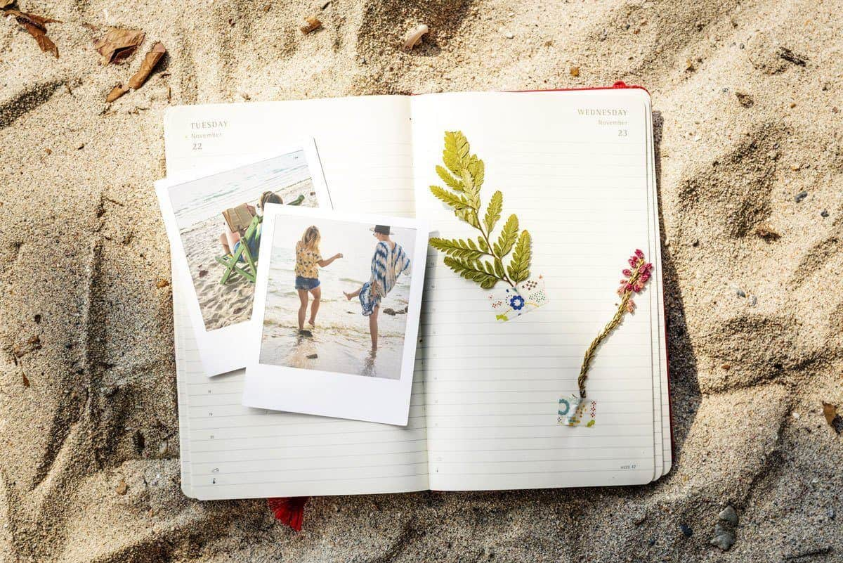diary laying on sand with flowers and photographs. travellers often ask how to Reduce Homesickness Abroad. we have some of the Best Home Comforts for Travel
