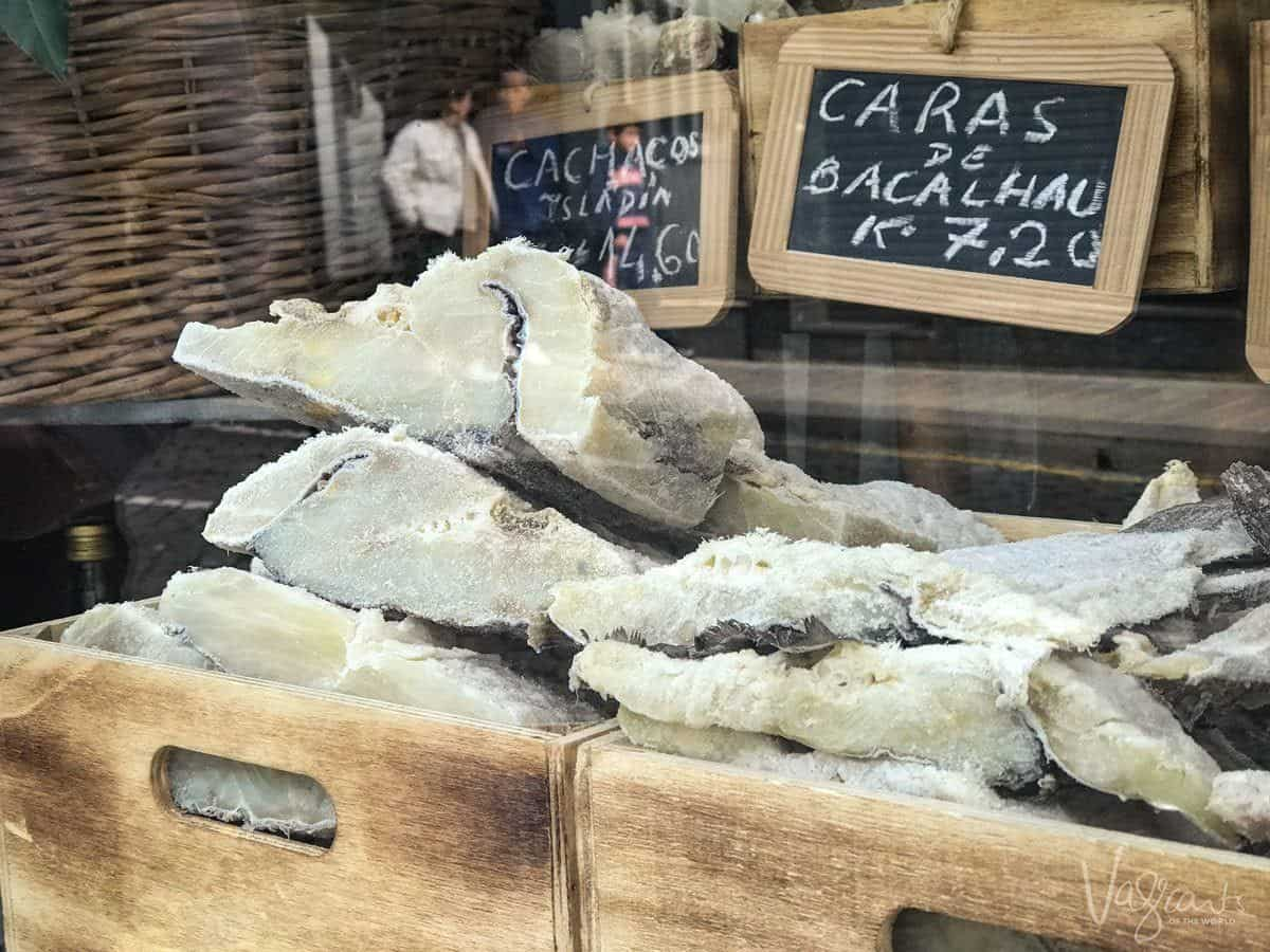 Eat traditional Bacalhau like these pieces in a wooden box at the front of a shop.