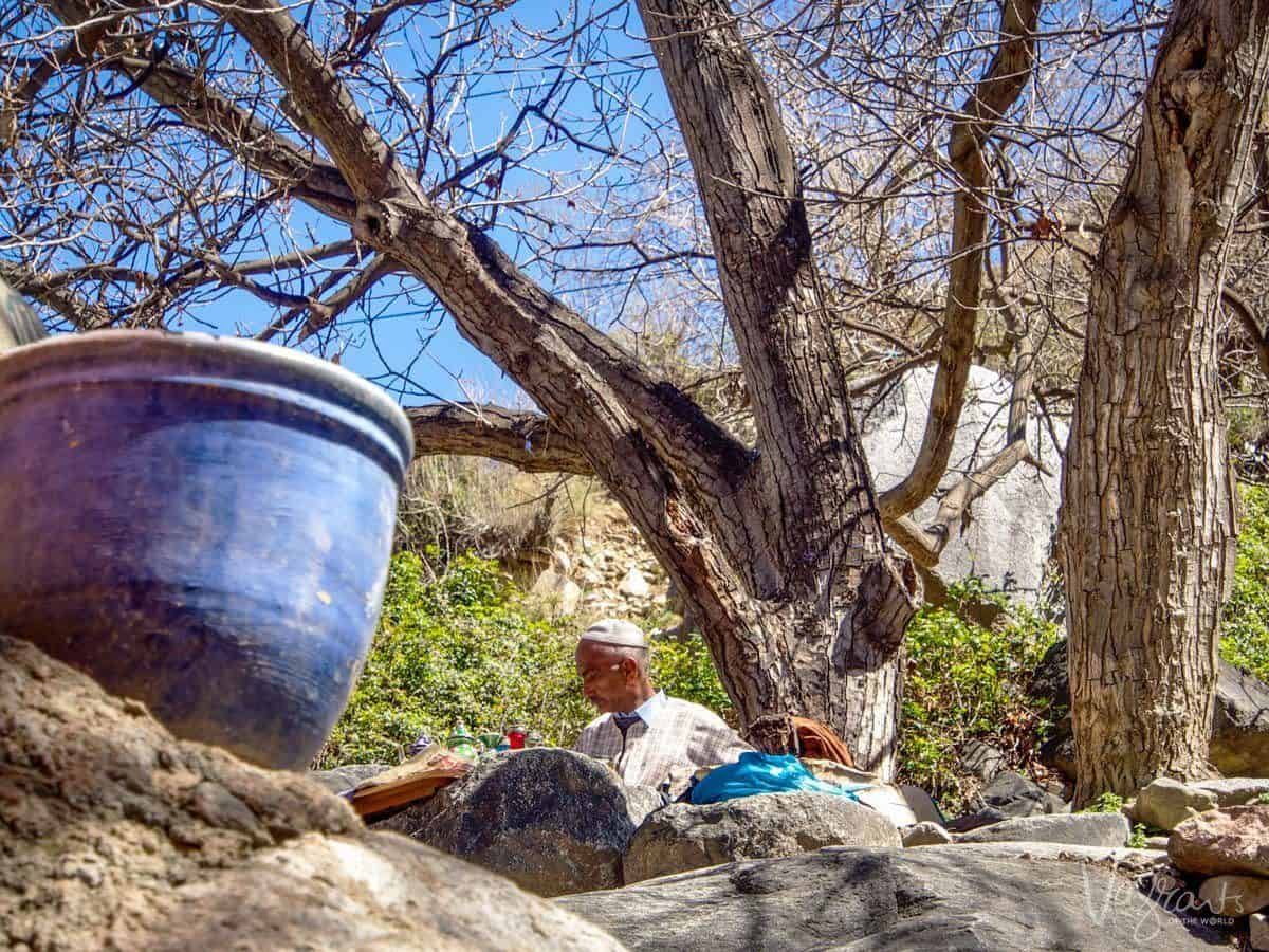 Vendor tending his wares behind a rocky outcrop and large blue pot.