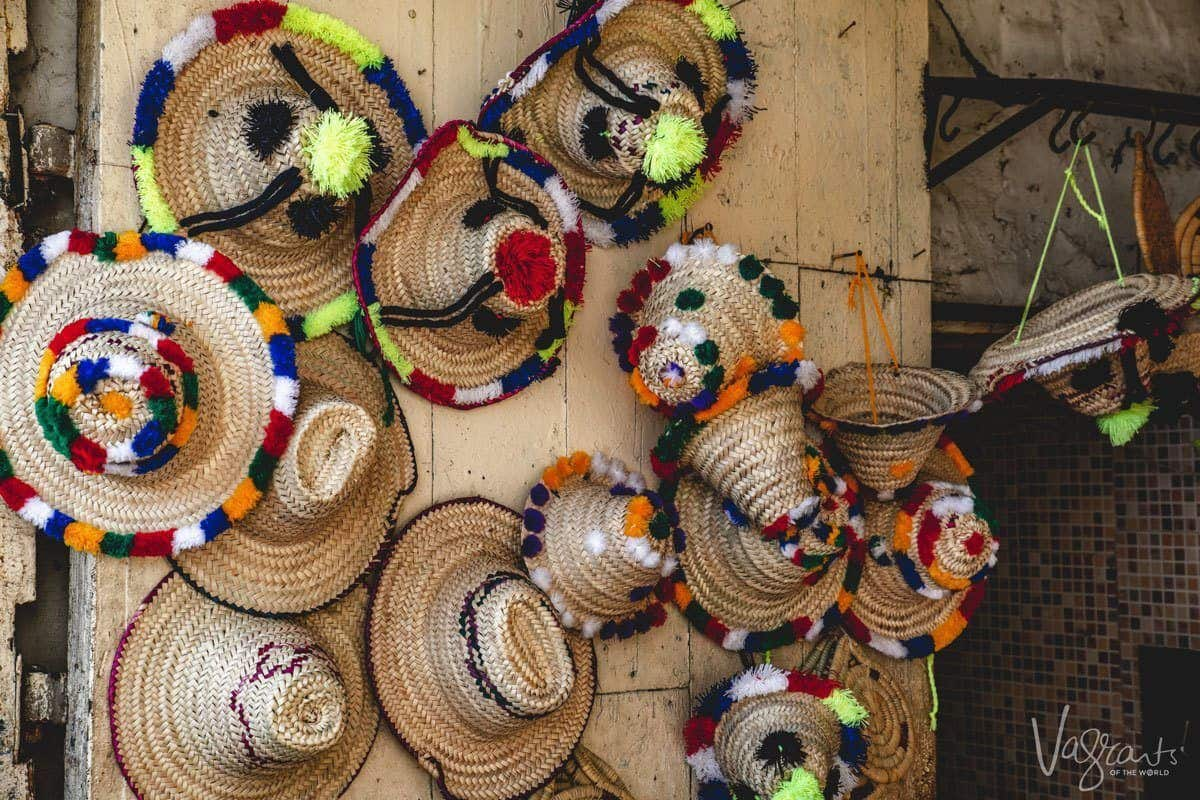Colourfully embroidered straw hats hanging on a wooden wall for sale in a medina.