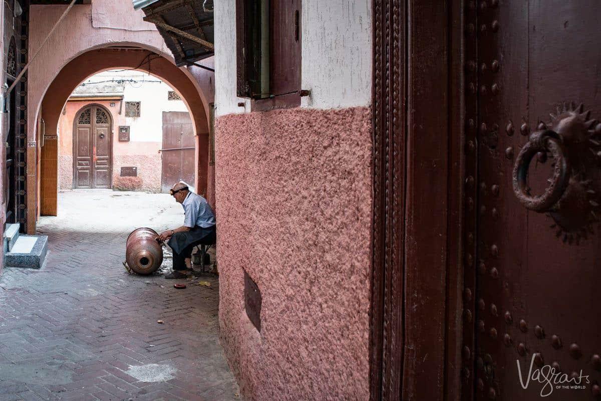 Man in alley working on copper drum in medina, Fez.
