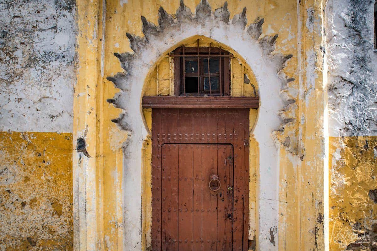 Old wooden door behind sunflower shaped yellow archway.