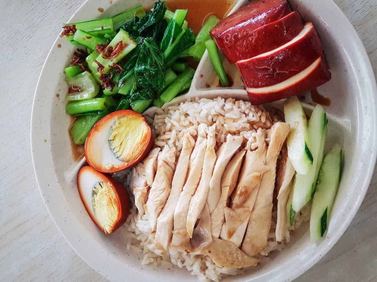 Plate of chicken and rice with egg and green veg.
