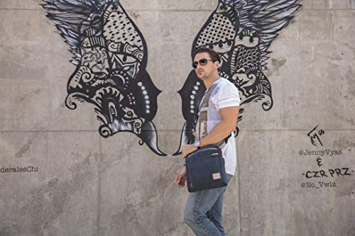 man with low slung cross body travel bag walking in front of eagle street art. These are the best cross body travel bags as they are also the right size for carry-on luggage as well. the anti-theft properties of cross body bags for travel are that they sit close to the body and near your hand.