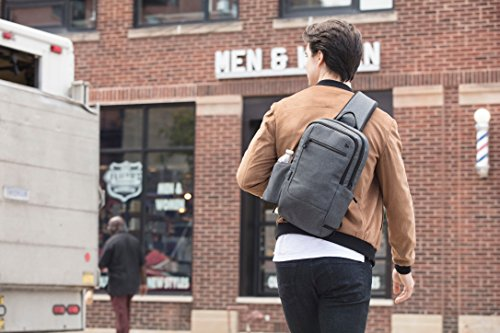 Man with grey crossbody shoulder bag worn more like a backpack. this is the perfect style of crossbody travel bag for men as it can hold more gear and is still easy to carry and to use as carry-on luggage.