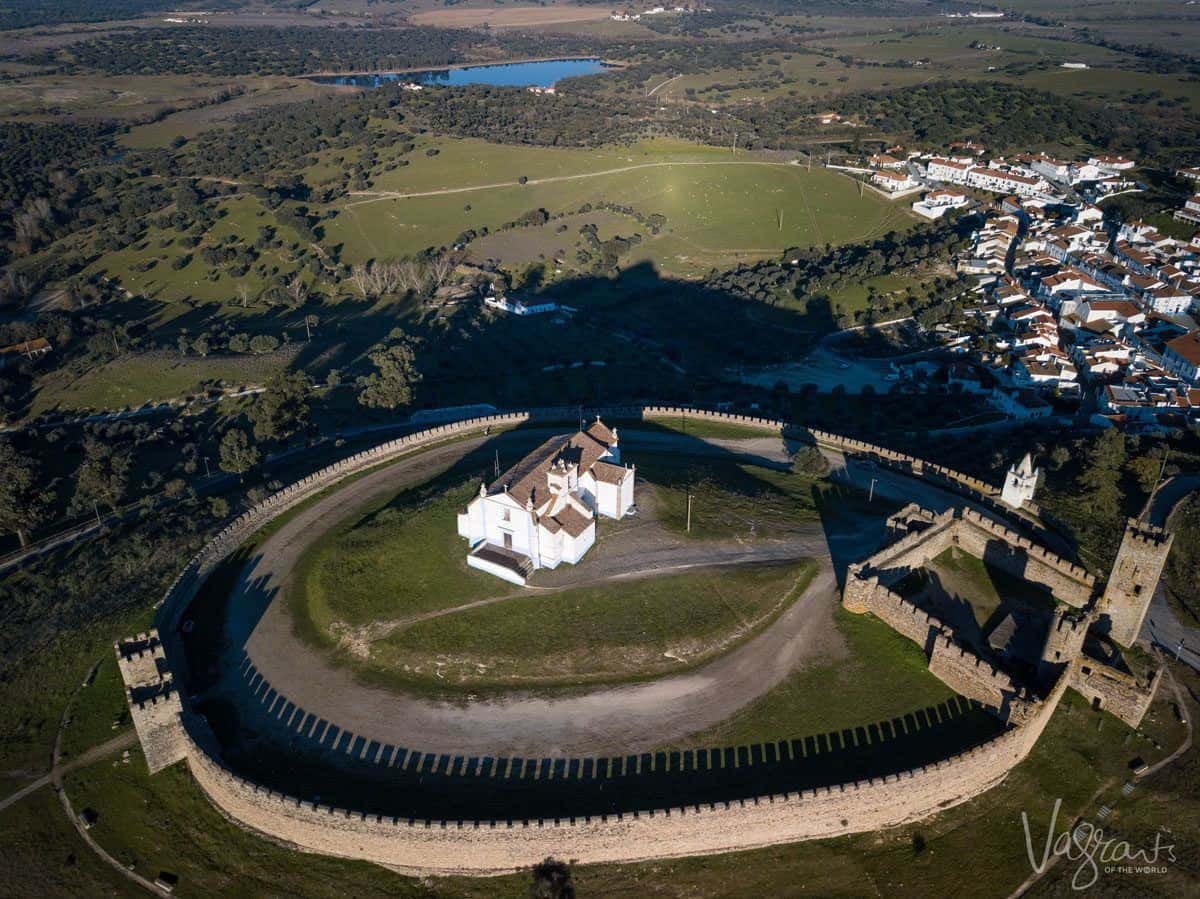 arial view of a circular castle with white church in the middle.  Looking for alentejo portugal highlights then this is certainly the place to stop on your alentejo road trip