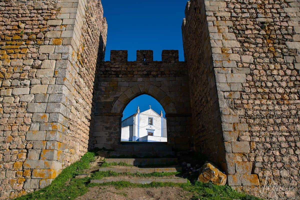 alentejo highlights are the castles such as this Arraiolos Castle with a white church seen behind the castles arch.  if you just want to do a day trip  from evora it is only a short drive and a must stop on your alentejo road trip