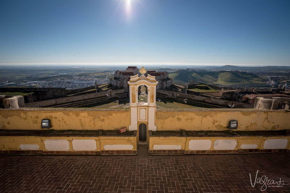 looking down over yellow and white church onto the city of Evora.  Make a stop in Evora on your Alentejo road trip as evora is one of the best places to visit in alentejo portugal
