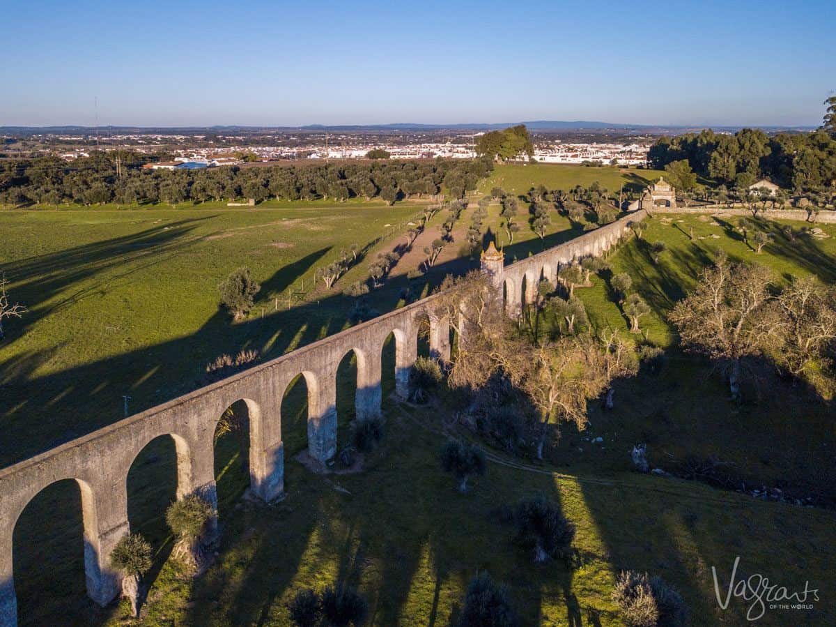 Ancient stone aqueducts dividing a green field, a alentejo highlight. These can be seen on a day trip from evora or on a alentejo portugal road trip.