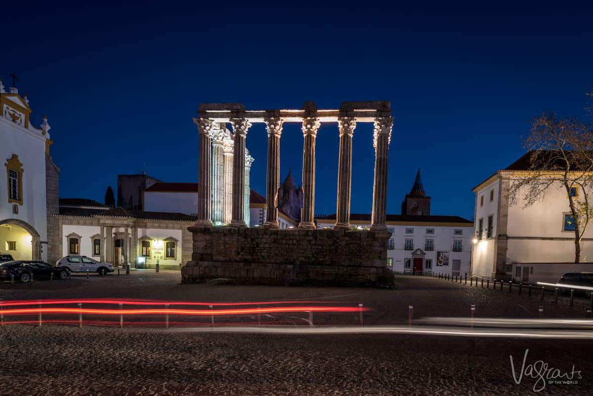 pillars of roman temple lit at night.