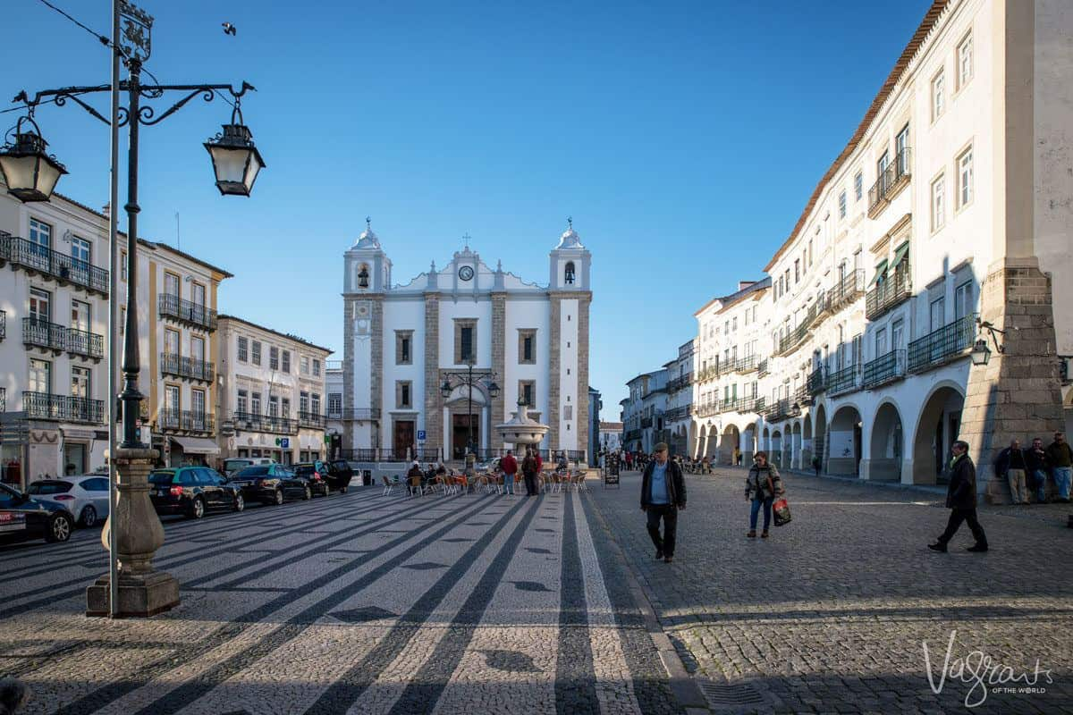 Evora square with mosaic cobblestones and white church. you can stop here for lunch and a bottle of alentejo wine on your lisbon to evora day trip or at the start of your alentejo road trip.