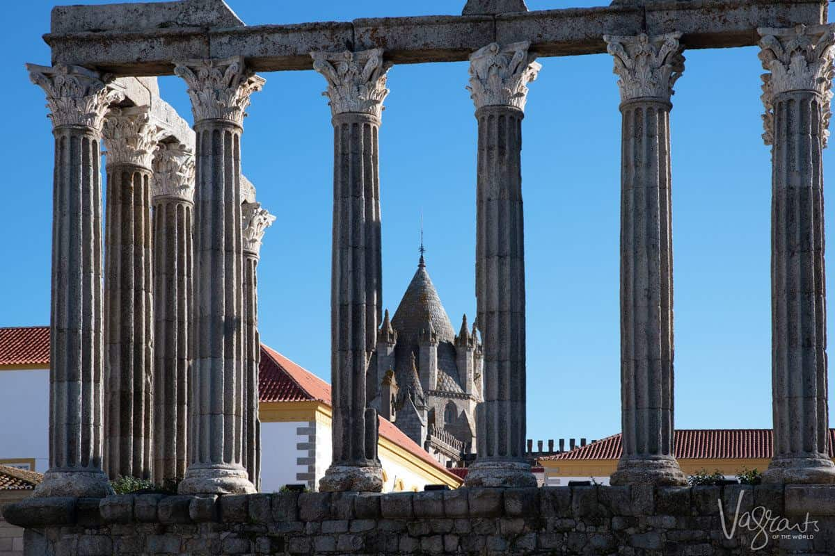 Pillars of the Roman temple of Diana with the church of bones in the background.  looking for something to do then take a lisbon to evora day trip and enjoy some of these alentejo highlights.