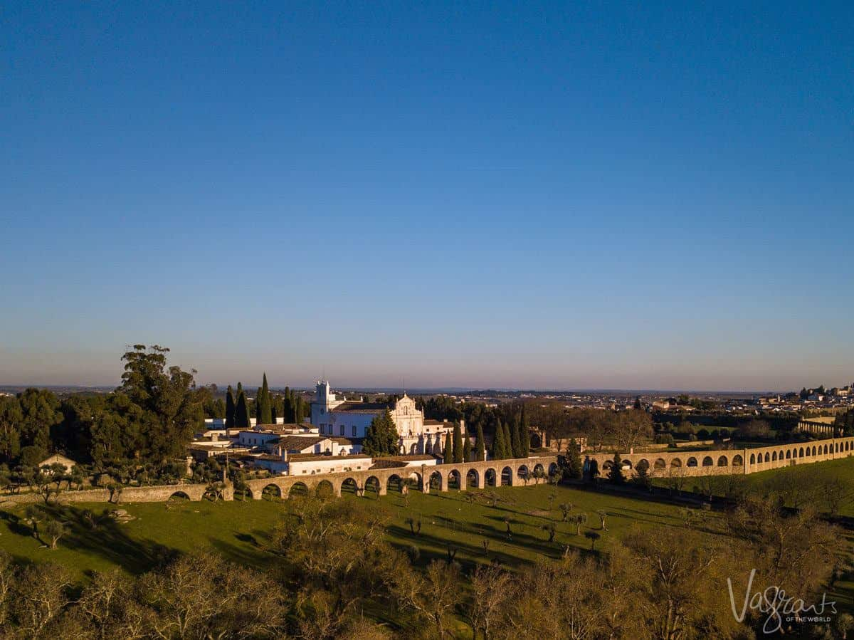 The aqueduct in Evora runs through the countryside and past an old monastery.