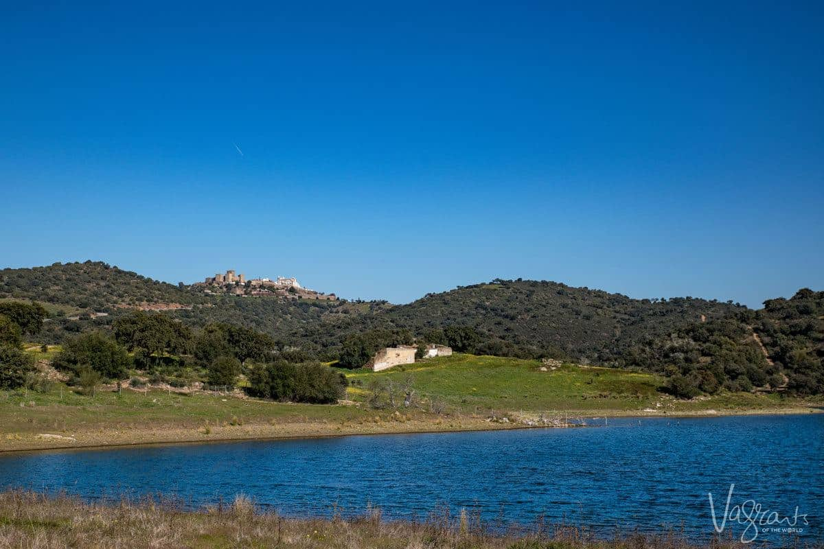the blue waters of Alqueva lake with hillside village in the background. Stop here for a lunch of alentejo food and wine on your alentejo portugal road trip