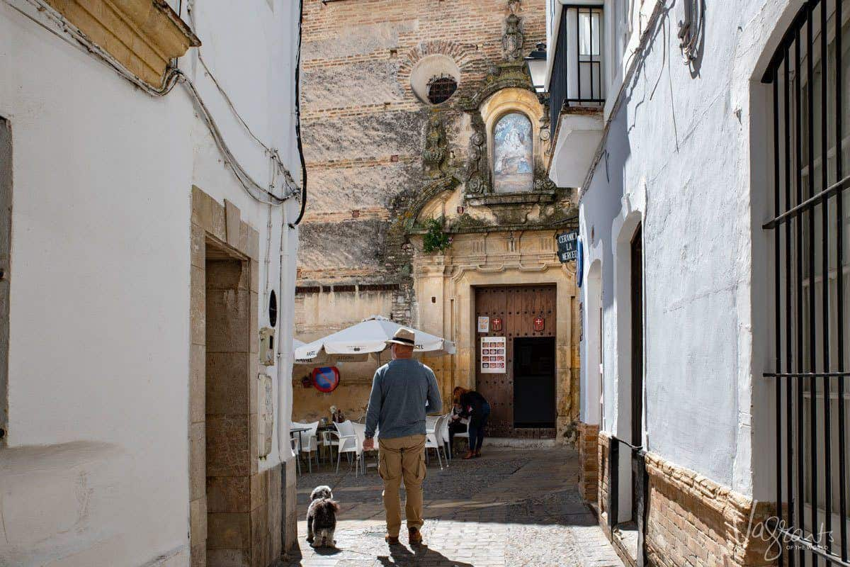 man in hat with dog outside a church during a tour of the white villages spain.